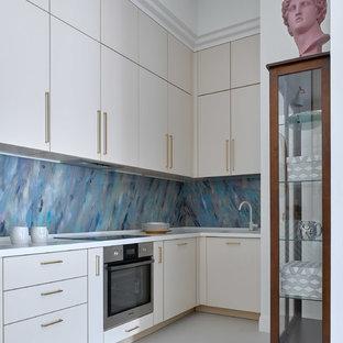 На фото: со средним бюджетом маленькие угловые кухни в современном стиле с врезной раковиной, плоскими фасадами, бежевыми фасадами, столешницей из акрилового камня, фартуком из стекла, техникой из нержавеющей стали, бетонным полом, белой столешницей, серым полом и синим фартуком без острова