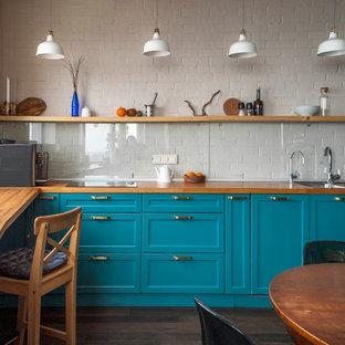 Идея дизайна: кухня в стиле неоклассика (современная классика) с обеденным столом, двойной раковиной, фасадами в стиле шейкер, бирюзовыми фасадами, деревянной столешницей, белым фартуком, фартуком из стекла, темным паркетным полом и коричневым полом