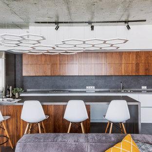 Новые идеи обустройства дома: кухня-гостиная в стиле лофт с плоскими фасадами, фасадами цвета дерева среднего тона, серым фартуком, островом, серым полом, монолитной раковиной, столешницей из нержавеющей стали, техникой из нержавеющей стали и бетонным полом