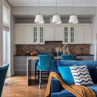Неиссякаемый источник вдохновения для домашнего уюта: большая линейная кухня в стиле современная классика с обеденным столом, фасадами с утопленной филенкой, серыми фасадами, столешницей из гранита, коричневым фартуком, фартуком из каменной плиты, паркетным полом среднего тона, островом, коричневым полом, врезной раковиной и техникой из нержавеющей стали