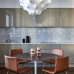На фото: кухня в современном стиле с плоскими фасадами, серым фартуком и коричневым полом с