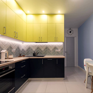 Modelo de cocina en L, contemporánea, pequeña, cerrada, sin isla, con fregadero de un seno, electrodomésticos de acero inoxidable, suelo de baldosas de porcelana, armarios con paneles lisos, puertas de armario amarillas, encimera de madera, salpicadero verde, suelo blanco y encimeras beige