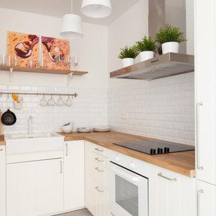 Идея дизайна: угловая кухня в скандинавском стиле с раковиной в стиле кантри, плоскими фасадами, белыми фасадами, деревянной столешницей, белым фартуком, фартуком из плитки кабанчик, серым полом и коричневой столешницей без острова