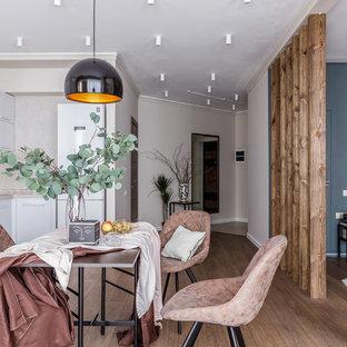 Diseño de cocina en L, actual, abierta, con armarios con paneles lisos, puertas de armario blancas, salpicadero beige, electrodomésticos blancos, suelo marrón y encimeras beige