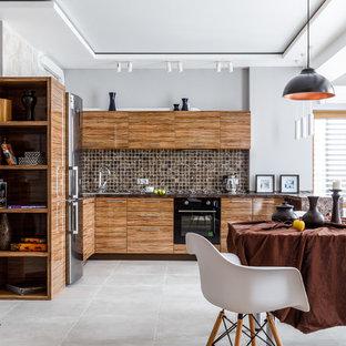 Пример оригинального дизайна: угловая кухня-гостиная в современном стиле с накладной раковиной, плоскими фасадами, фасадами цвета дерева среднего тона, коричневым фартуком, фартуком из плитки мозаики, черной техникой, полуостровом, серым полом и коричневой столешницей
