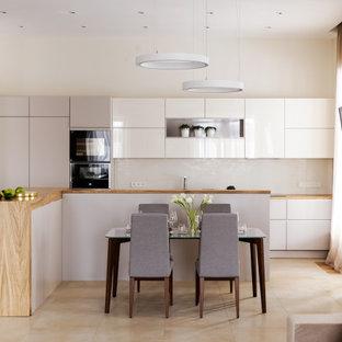 Идея дизайна: прямая кухня в современном стиле с обеденным столом, плоскими фасадами, белыми фасадами, бежевым фартуком, черной техникой, островом, бежевым полом и коричневой столешницей