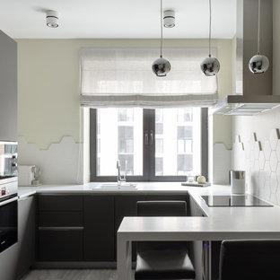 На фото: п-образная кухня-гостиная среднего размера в современном стиле с накладной раковиной, плоскими фасадами, серыми фасадами, столешницей из акрилового камня, белым фартуком, полом из ламината, серым полом, белой столешницей, фартуком из керамической плитки и черной техникой с