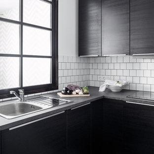 Inredning av ett modernt avskilt, litet kök, med laminatbänkskiva, vitt stänkskydd, stänkskydd i keramik, klinkergolv i porslin, flerfärgat golv, en nedsänkt diskho, släta luckor och svarta skåp