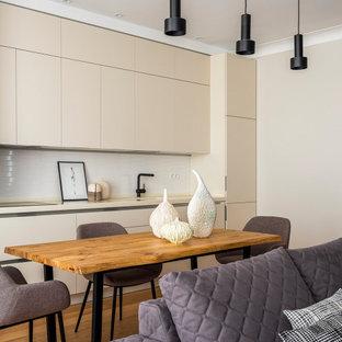 Стильный дизайн: большая прямая кухня-гостиная в современном стиле с плоскими фасадами, бежевыми фасадами, белым фартуком, паркетным полом среднего тона, коричневым полом и бежевой столешницей - последний тренд