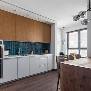 Удачное сочетание для дизайна помещения: линейная кухня в современном стиле с обеденным столом, врезной раковиной, плоскими фасадами, серыми фасадами, техникой из нержавеющей стали, полуостровом, коричневым полом и белой столешницей - самое интересное для вас