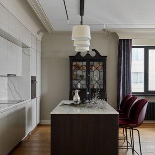 На фото: прямая кухня-гостиная среднего размера в стиле современная классика с коричневым полом, плоскими фасадами, серыми фасадами, белым фартуком, черной техникой, островом и белой столешницей