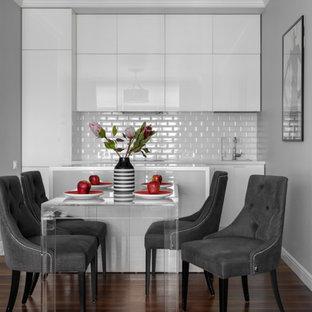 Свежая идея для дизайна: параллельная кухня в современном стиле с плоскими фасадами, белыми фасадами, белым фартуком, фартуком из плитки кабанчик, островом, коричневым полом, белой столешницей и темным паркетным полом - отличное фото интерьера