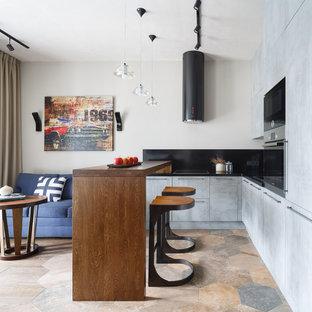 Идея дизайна: п-образная кухня-гостиная в современном стиле с накладной раковиной, плоскими фасадами, серыми фасадами, столешницей из кварцевого агломерата, черным фартуком, полуостровом, бежевым полом, черной столешницей, полом из керамогранита и техникой под мебельный фасад