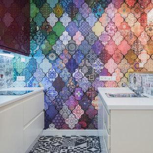 На фото: параллельная кухня в современном стиле с двойной раковиной, плоскими фасадами, белыми фасадами, разноцветным фартуком, черной техникой, полом из цементной плитки, разноцветным полом и белой столешницей с