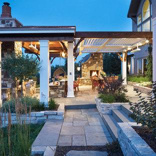 Großer Klassischer Garten hinter dem Haus mit Kamin, direkter Sonneneinstrahlung und Pflasterklinker in Minneapolis