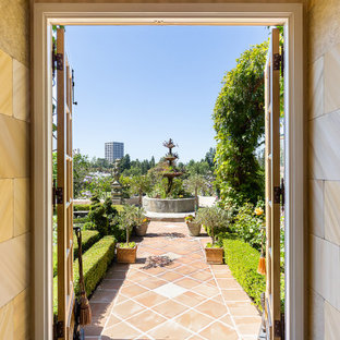 This is an example of a huge french country full sun backyard landscaping in Orange County.