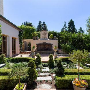 Geometrischer, Geräumiger Garten hinter dem Haus mit Kamin, direkter Sonneneinstrahlung und Natursteinplatten in Orange County