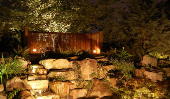 A backyard with landscape lighting for pond area