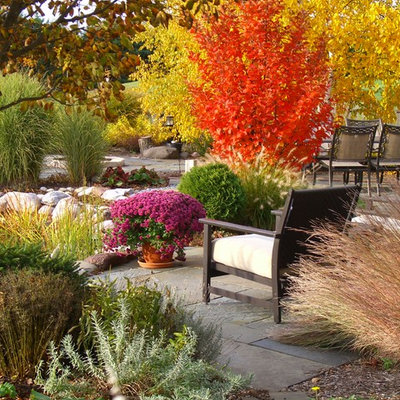 Inspiration for a huge traditional partial sun backyard stone landscaping in Milwaukee.