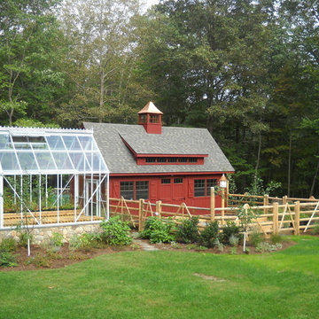 A greenhouse, barn and vegetable garden