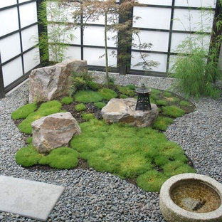 Small asian courtyard garden in Hamilton with a water feature and gravel.