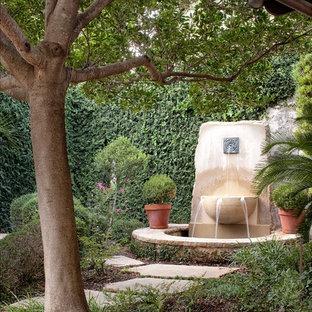 Ejemplo de jardín mediterráneo con adoquines de piedra natural y fuente