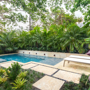 Photo of a mid-sized beach style backyard formal garden in Miami.