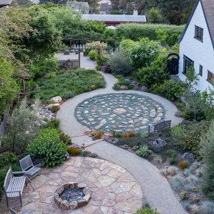 Réalisation d'un grand xéropaysage arrière design au printemps avec un foyer extérieur, une exposition ensoleillée et des pavés en pierre naturelle.