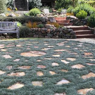 Exempel på en stor modern bakgård i full sol som tål torka på våren, med en öppen spis och naturstensplattor