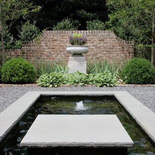 Diseño de jardín clásico, de tamaño medio, en patio lateral, con fuente y gravilla