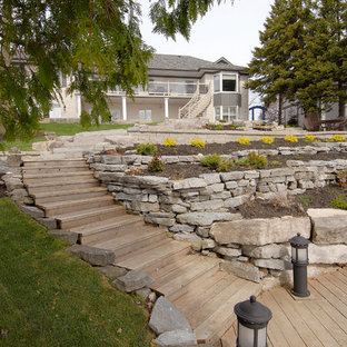 Photo of a large traditional full sun backyard retaining wall landscape in Toronto with decking.