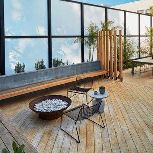На фото: большой солнечный засухоустойчивый сад на заднем дворе в стиле модернизм с местом для костра, хорошей освещенностью и настилом с