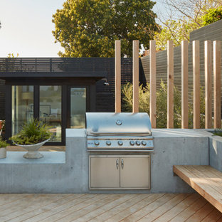 Inspiration for a large modern drought-tolerant and full sun backyard landscaping with a fire pit and decking.