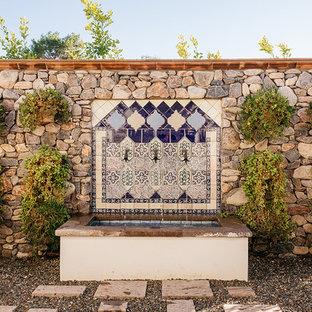 Новые идеи обустройства дома: огромный геометрический садовый фонтан на боковом дворе в средиземноморском стиле с покрытием из каменной брусчатки