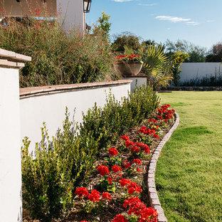 Cette photo montre un très grand jardin à la française arrière méditerranéen avec des pavés en brique et un massif de fleurs.