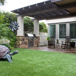 Großer Landhaus Garten hinter dem Haus mit Kamin, direkter Sonneneinstrahlung und Betonplatten in Orange County
