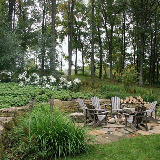 This is an example of a large rustic back formal partial sun garden in Philadelphia with a fire feature and natural stone paving.