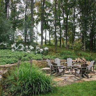 На фото: большой геометрический участок и сад на заднем дворе в стиле рустика с местом для костра, покрытием из каменной брусчатки и полуденной тенью