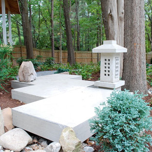 Inspiration for an asian backyard garden in Charlotte with concrete pavers and with rock feature.