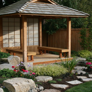 Idée de décoration pour un jardin avec une terrasse en bois ou composite asiatique.