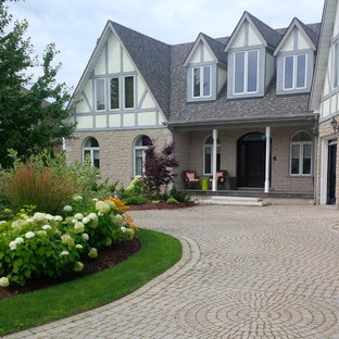 Large traditional front yard full sun driveway in Toronto with brick pavers for summer.