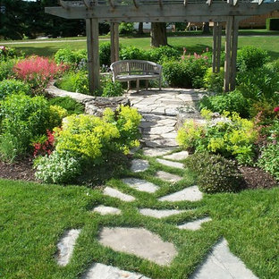 Design ideas for a large contemporary partial sun backyard stone landscaping in Toronto for summer.