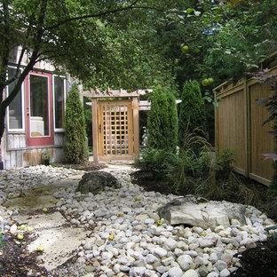 Réalisation d'un jardin latéral design avec des solutions pour vis-à-vis et des galets de rivière.