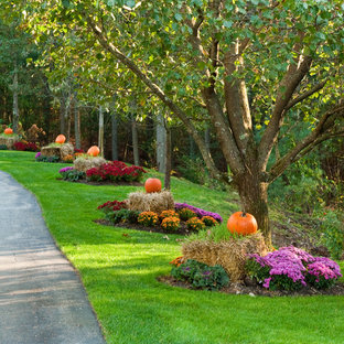 This is an example of a traditional front yard driveway for fall in Boston with with flowerbed.