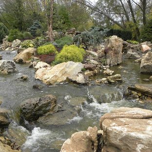 Photo of a huge traditional partial sun backyard stone water fountain landscape in Chicago for summer.