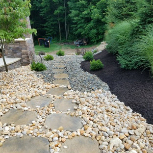 Photo of a huge craftsman full sun backyard landscaping in Other with a fireplace.