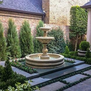 Foto de jardín francés, mediterráneo, de tamaño medio, en patio trasero, con fuente y adoquines de piedra natural