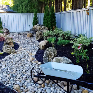 Design ideas for a mid-sized traditional partial sun backyard river rock landscaping in Toronto for summer.