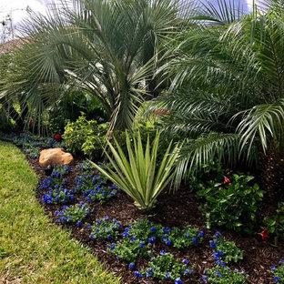 Inspiration for a mid-sized tropical partial sun backyard mulch formal garden in Orlando.