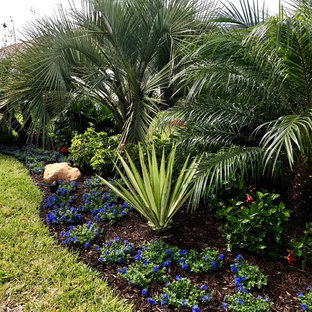 This is an example of a mid-sized tropical partial sun backyard mulch formal garden in Orlando.
